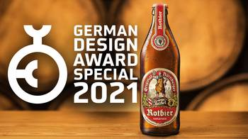 [Translate to EN:] Tucher Rotbierflasche vor Fasshintergrund mit German Design Award Special 2021 Logo